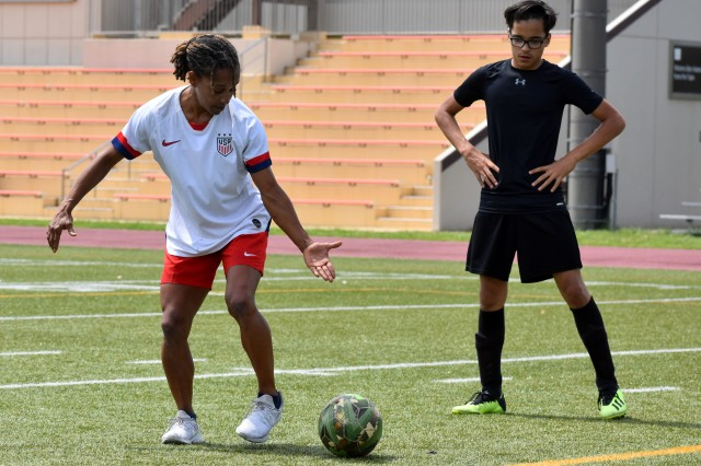 Staci Wilson, a former United States women's national soccer team player and a gold medal winner as a member of the 1996 U.S. Olympic Team, works with a soccer player on his game during a soccer clinic at Camp Zama, Japan, June 14.