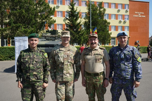 """U.S. Army Soldiers from the 1st Squadron, 2d Cavalry Regiment, 2nd Lt. Bogdan Aioanei, public affairs officer, Romanian Land Forces, Col. Bradley A. Heston, U.S. Army, Dr. Ghita Barsan, rector and commandant of the Romanian """"Nicolae Balcescu"""" Land Forces Academy, Sibiu, Romania and Capt. Robert Stanciu, counter intelligence officer, NATO Forces Integration Unit Romania,  participate in the Saber Guardian 2019 static display in Sibiu, Romania, June 15, 2019. SG19 is an exercise co-led by the Romanian Land Forces & U.S. Army Europe, taking place from June 3 - 24 at various locations in Bulgaria, Hungary & Romania. SG19 is designed to improve the integration of multinational combat forces."""