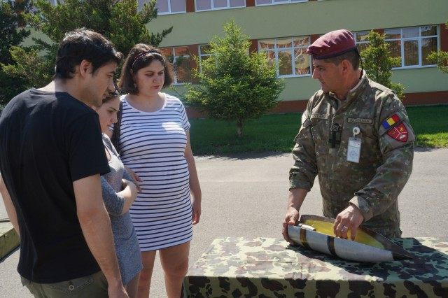 A Romanian Land Forces Soldier discusses the shell for the 152mm towed howitzer during the 1st Squadron, 2d Cavalry Regiment's Saber Guardian 2019 static display in Sibiu, Romania, June 15, 2019. SG19 is an exercise co-led by the Romanian Land Forces & U.S. Army Europe, taking place from June 3 - 24 at various locations in Bulgaria, Hungary & Romania. SG19 is designed to improve the integration of multinational combat forces.