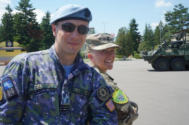 Capt. Robert Stanciu, counter intelligence officer, Romanian Air Force and U.S. Army 1st Lt. Ellen Brabo, public affairs officer, 2d Cavalry Regiment, exchange unit patches during 1st Squadron, 2d Cavalry Regiment's Saber Guardian 2019 static display in Sibiu, Romania, June 15, 2019. SG19 is an exercise co-led by the Romanian Land Forces & U.S. Army Europe, taking place from June 3 - 24 at various locations in Bulgaria, Hungary & Romania. SG19 is designed to improve the integration of multinational combat forces.