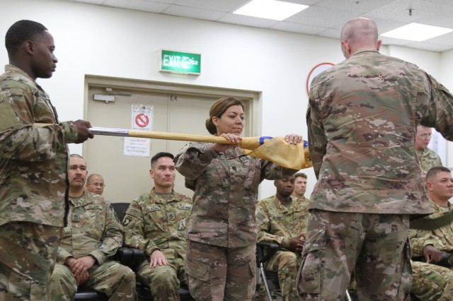 Lt. Col. Maria Carrillo, 320th Quartermaster Detachment commander, uncases the unit guidon at Camp Arifjan, Kuwait, June 8, 2019. (U.S. Army National Guard photo by Sgt. Ashley Breland)