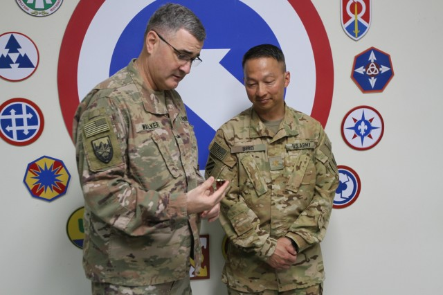 Brig. Gen. Clint E. Walker, commanding general of 184th Sustainment Command, shares the meaning of his challenge coin to Maj. Timothy Bird at Camp Arifjan, Kuwait, June 8, 2019. (U.S. Army National Guard photo by Sgt. Ashley Breland)