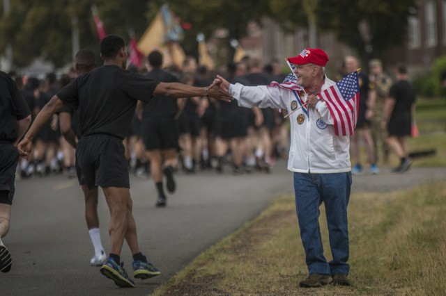 A veteran and a Soldier of I Corps exchange a passing greeting during the  I Corps Army birthday run at Joint Base Lewis-McChord June 14.