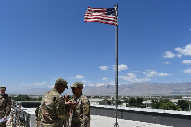 COL Robert L. McDonald, ACC-A Commander, pins the Superior Civilian Service Award on Mr. Kelvin Magee after his two years of service as the ACC-A deputy in Afghanistan.