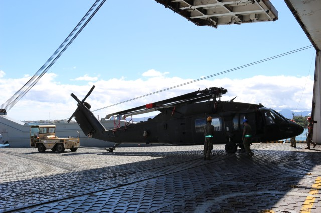 Members of the 25th CAB offload a Black Hawk helicopter during port operations on the M/V Cape Hudson at Pearl Harbor on June 12.