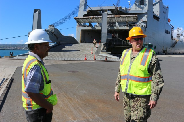 From left: Davey Flores, 599th traffic management specialist, and Navy Cmdr. Keith Applegate, 599th director of operations, discuss the move during port operations on the M/V Cape Hudson at Pearl Harbor on June 12.