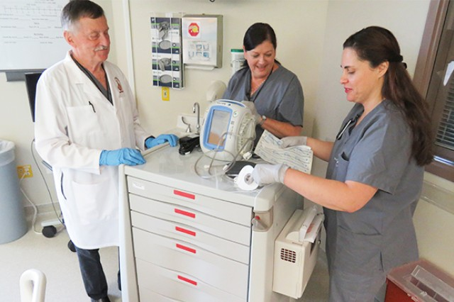 Dr. Charles Andersen and nurses Joanie Santucci and Eloa Reid with Madigan's Wound Care Service prepare a Wound Vacuum-Assisted Closure device on June 12. The service's inpatient team stood up six months ago to provide dedicated wound care expertise to inpatients.