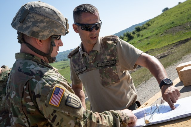An engineer from the West Virginia Army National Guard (WVARNG) looks over plans with a Romania soldier June 19, 2019, at the Cincu Training Area in Cincu, Romania. West Virginia Army National Guard engineers are participating in Resolute Castle 19, a multi-national joint exercise that conducts troop construction engineer projects and reinforces regional assurance and deterrence while strengthening partnership capacity with NATO allies.