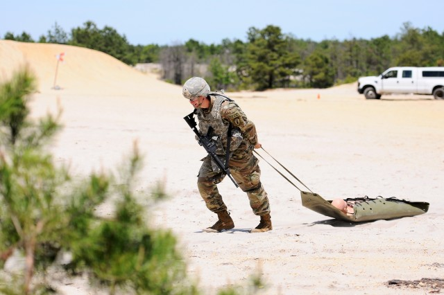Spc. Matthew Lofink, representing the 71st Ordnance Group, drags a 135-pound dummy through the sand as part of the Stress Shoot portion during the 20th Chemical, Biological, Radiological, Nuclear, Explosives (CBRNE) Command's Best Warrior Competition. During the stress shoot, competitors had to complete several tasks such as carrying two 5-gallon jugs and a 30-meter tire flip among others before reaching the shooting area. The Best Warrior Competition is a 5-day event in were competitors test their knowledge, skills and abilities by conquering urban warfare simulations, demonstrating critical thinking, physical fitness challenges, written exams, warrior tasks and battle drills relevant to modern-day combat environments.