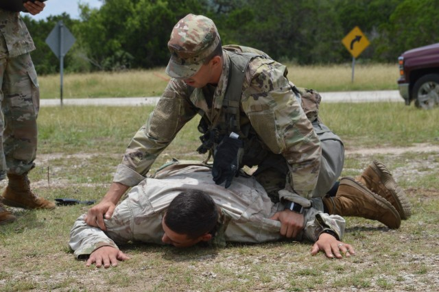 Army Sgt. Kevin Ramirez takes down an aggressor June 12, 2019 during the tactical road march portion of the Brooke Army Medical Center Best Medic Competition at Camp Bullis, Texas. The competitors were tested on both warrior and medic skills during the competition.