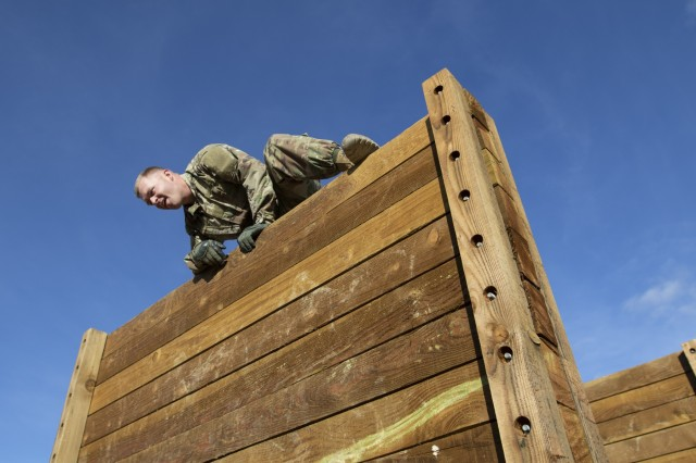 Cpl. Micah Barton, a combat medic assigned to Company A., 1st Battalion, 4th Security Forces Assistance Brigade, climbs over a wall during the obstacle course at the post's Best Warrior Competition, Fort Carson, Colorado, April 25, 2019. The competition is a multi-day, annual event designed to test the physical fitness, military knowledge, marksmanship, and endurance of each competitor. (U.S. Army photo by Pvt. Ashton Empty)