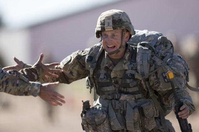 Cpt. Andrew Taylor, assigned to 10th Field Hospital, 627th Hospital Center, returns high-fives from Soldiers as he approaches the finish line of a 12-mile ruck march during the 2019 Fort Carson Expert Field Medical Badge event April 19, 2019, Fort Carson, Colorado. The EFMB is the non-combat equivalent of the Combat Medical Badge and is awarded to medical personnel of the U.S. military who successfully complete a set of qualification tests. (U.S. Army photo by Sgt. Micah Merrill)