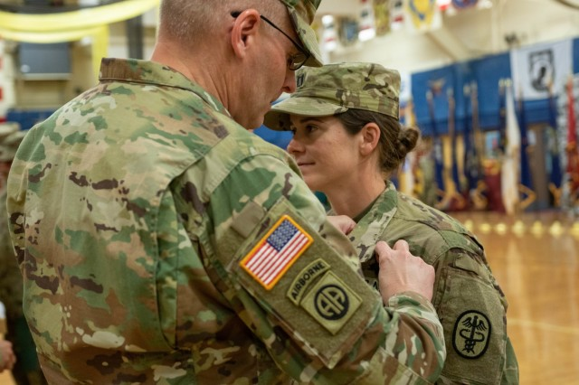 """Brig. Gen. Jeffrey Johnson, commanding general of Regional Health Command, pins the Expert Field Medical Badge on Cpt. Mary Wallace, assigned to Medical Department Activity, 4th Infantry Division, during the award ceremony held at the William """"Bill"""" Reed Special Events Center, Fort Carson, Colorado, April 19, 2019. The EFMB is the non-combat equivalent of the Combat Medical Badge and is awarded to medical personnel of the U.S. military who successfully complete a set of qualification tests. (U.S. Army photo by Sgt. Daphney Black)"""