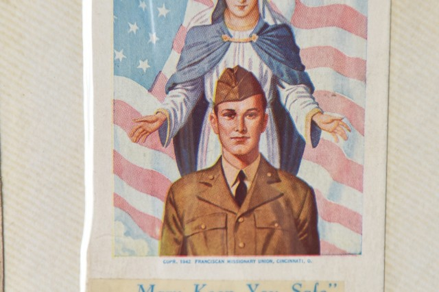 """A religious card taped into a scrapbook compiled by Aida Bonsonto showcases her husband's military service during World War II. When Bonsonto found out her future husband had been wounded while fighting in Europe she went to Holy Family Church in Chicago and crawled the length of the aisle leading to the altar. """"I asked God to spare his life,"""" said Bonsonto. Jerry returned home and the two were married in Holy Family Church on June 8, 1946. (U.S. Army Reserve photo by Sgt. David Lietz)"""