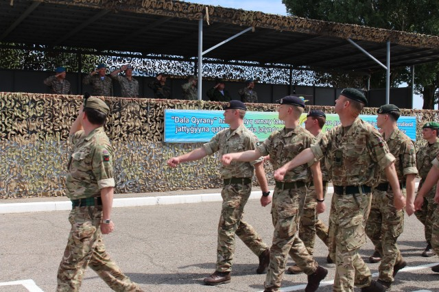 British Army soldiers march during the Steppe Eagle 19 opening ceremony's Pass-and-Review, June 17, 2019, as the leaders for each national contingent salute the passing formations of nearly 400 troops. Steppe Eagle 19 is an annual U.S. Army Central-led exercise that promotes regional stability and interoperability in the Central and South Asia region.