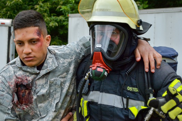 A German firefighter from the Landkreis Kaiserslautern fire department assist an injured U.S. Army Soldier during a simulated train derailment and mass casualty decontamination operation, June 15, near Landstuhl, Germany. This real-world training scenario was part of Maroon Response 19, designed to enhance the ready medical force and strengthen the relationship between U.S. and German emergency response personnel.