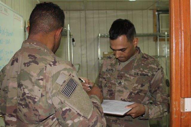 Staff Sgt. Govinda L. Acuna ensures Sgt. Christopher J. Webster signs for a box after picking it up from the 595th Transportation Brigade mail room at Camp Arifjan, Kuwait, June 4, 2019. (U.S. Army photo by Claudia LaMantia)