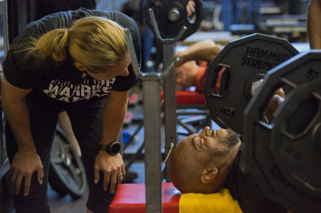 U.S. Army Retired, Spc. Brent Garlic, lifting weights during the Powerlifting practice portion as Coach Andriane Wilson observes on June 18, 2019, at MacDill Airforce Base, Florida during the 2019 Department of Defense Warrior Games. The DoD Warrior Games are conducted June 21- 30, hosted by Special Operations Command, Tampa, Florida. It is an adaptive sports competition for wounded, ill and injured service members and veterans. Approximately 300 athletes representing teams from the Army, Marine Corps, Navy, Air Force, Special Operations Command, United Kingdom Armed Forces, Armed Forces of the Netherlands, and the Danish Armed Forces will compete in archery, cycling, shooting, sitting vollyball, swimming, track, field, wheelchair basketball, indoor rowing, powerlifting, and for the first time in Warrior Games history, golf, wheelchair tennis, wheelchair rugby, and mountain biking. (U.S. Army photo by Spc. Samantha Ruiz)