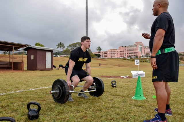 Sgt. 1st Class Jarrod Vining, right, noncommissioned officer in charge, Department of Physical Medicine & Rehabilitation, Tripler Army Medical Center (TAMC), coaches Sgt. Dominic Falzarano, left, cash control NCOIC, TAMC Nutrition Care Department, during a Spartan Army Combat Physical Training course at the TAMC Track, April 17. (U.S. Army photo by Leanne Thomas)