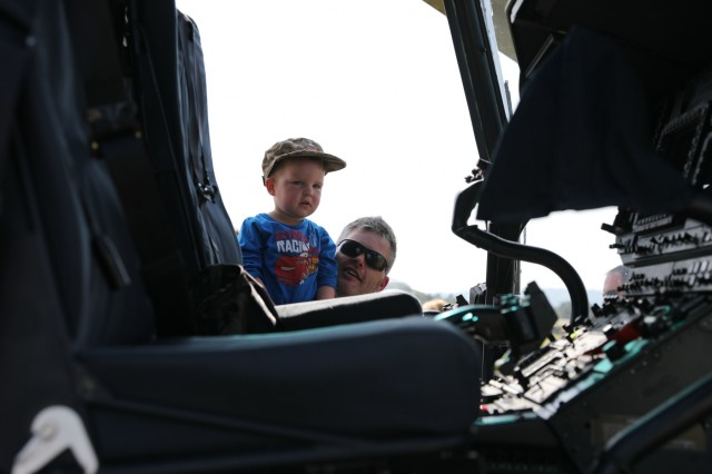 A visitor lifts his child to see inside a Slovenian military aircraft at a community engagement event June 8, 2019 in Divaca, Slovenia. The event showcased both the U.S. and Slovenian militaries' equipment and included static displays and live demonstrations. U.S. Army photo by Sgt. Erica Earl