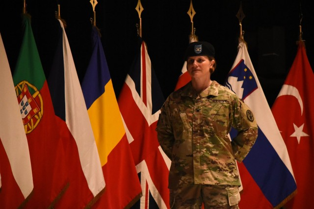 """Army Col. Kathleen G. Spangler passed the unit guidon to Sgt. 1st Class Ricardo Nathan, clinic detachment sergeant, to signify her assumption of command of the SHAPE Healthcare Facility and Brussels Army Health Clinic June 19, 2019, during a ceremony at the SHAPE Alliance Auditorium at SHAPE, Belgium. Spangler replaced Army Col. Yolonda """"YR"""" Summons who assumed command in June 2017 and will serve as the deputy chief of the Medical Service Corps."""