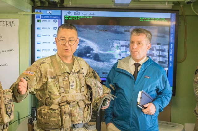 Gregg Thompson, Maneuver Support Center of Excellence deputy to the commanding general, right, receives a brief from Col. Kevin Fujimoto, Missouri National Guard's 110th Maneuver Enhancement Brigade commander, during the Combined Arms Live Fire Exercise June 10 at Fort Leonard Wood.