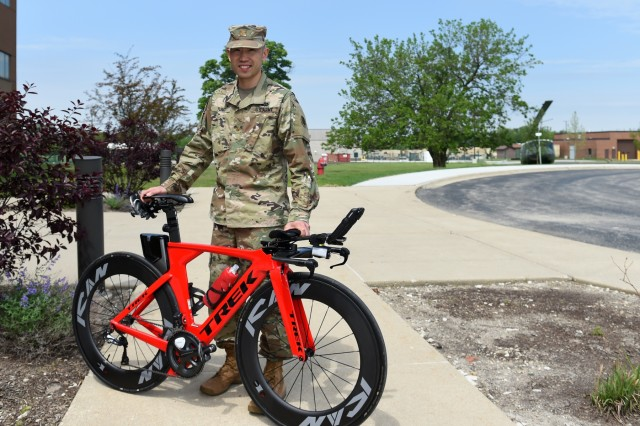 Maj. Christopher Tung pauses for a photo with his speed bicycle. Tung said the geometry and aerodynamics of the bike make it 'really fast'. He has used this bicycle for the past few years. Handle bars are one of the main differences between a road bike and triathlon bike. Triathlon bikes have aerobars instead of regular handles. Triathlon bikes are also intended for riding on roads and use a thinner frame and tire for greater efficiency. (U.S. Army Reserve photo by Sgt. David Lietz)