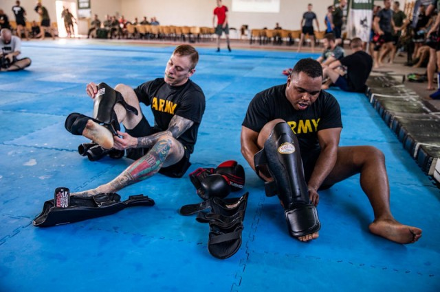 278th Armored Cavalry Regiment HHT Commander, Cpt. Cory Mondschein (left) and Sgt. Alvin Williams put on leg pads during a mixed martial arts seminar hosted by the Polish 15th Mechanized Brigade in Gizycko, Poland, June 11.