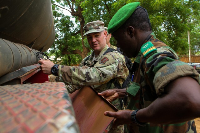Indiana Air Guard Senior Master Sgt. Justin D. Scheumann, a fueling operations specialist, and Nigerien Maj. Issoufou M. Mahdio, from the Directorate of hydrocarbon operations, open a compartment on a fuel truck during the site visit component of Operation Hydrocarbon June 12, 2019, at Camp Badage, Niger. The operation was a five-day exercise with a goal of exchanging tactic, procedures, and techniques for fuel, logistical, and maintenance operations.