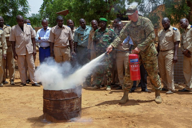 Indiana National Guard Staff Sgt. Cody Freeman, a grounds fuel operations specialist, demonstrates the proper technique for putting out a gas fire with a fire extinguisher during the site visit component of Operation Hydrocarbon June 12, 2019, at Camp Badage, Niger. The operation was a five-day exercise with a goal of exchanging tactic, procedures, and techniques for fuel, logistical, and maintenance operations.