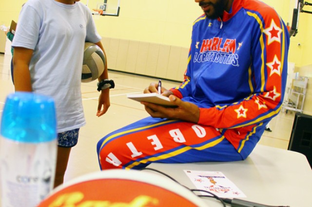 """Harlem Globetrotter Julian """"Zeus"""" McClurkin signs an autograph for a young fan after his motivational presentation to middle schoolers June 11, 2019, at the Fort Sill Youth Center."""