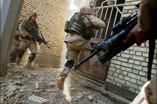 A member of the 1st Infantry Division attempts to kick down the door of a gateway in the streets of Fallujah. In November 2004, section of the city had been abandoned and taken over by insurgents who had ties to jihadist leader Abu Musab al-Zarqawi. Medal of Honor recipient David Bellavia would take part in some of the most vicious fighting of the Second Battle of Fallujah in the fall of 2004.