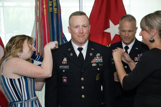 ABERDEEN PROVING GROUND, Md. - Chief Warrant Officer 4 Jamie Montgomery has his rank devices attached by his wife and daughter during his promotion ceremony in the U.S. Army Communications-Electronics Command headquarters.