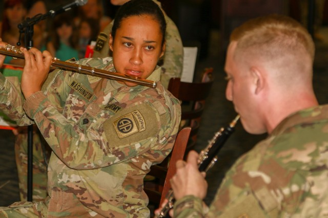 "U.S. Army Spc. Kaila Washington, assigned to the 82nd Airborne Division's woodwind quintet band, plays the flute during the summer reading program at the Throckmorton Library on Fort Bragg, North Carolina, June 19, 2019. The band played songs such as ""Ferdinand the Bull"" and ""How to Train Your Dragon"" while a band member read the story aloud. (U.S. Army photo by Pfc. Chantel Green)"