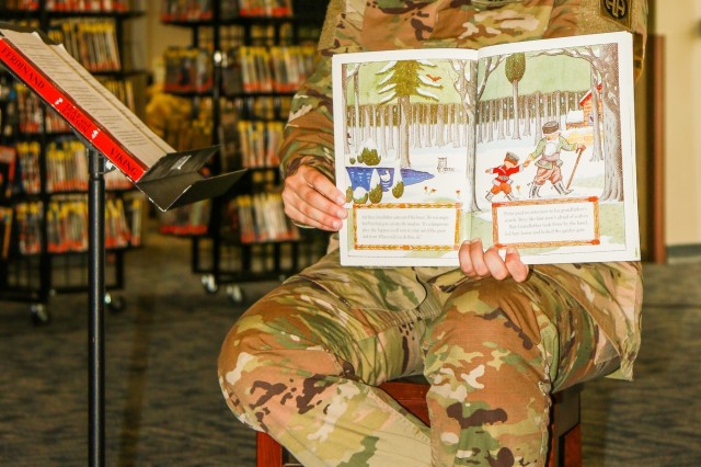 "U.S. Army Staff Sgt. Kathryn Beyer, assigned to the 82nd Airborne Division's woodwind quintet band, reads while the band performs during the summer reading program at the Throckmorton Library on Fort Bragg, North Carolina, June 19, 2019. Members of the band played music from ""Peter and the Wolf"", ""Pokemon"" and ""The Incredibles"" for an audience of more than 25 children and parents. (U.S. Army photo by Pfc. Chantel Green)"
