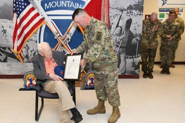 Col. Shane Morgan, 1st Brigade Combat Team commander, presents Don Waful, a Syracuse native and World War II veteran, with a certificate naming him an honorary member of 1st BCT during his visit June 20 to Fort Drum. (Photo by Mike Strasser, Fort Drum Garrison Public Affairs)