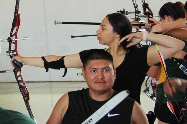 Spc. Kevin Holyan (foreground) and Pfc. Kyia Costanzo (background) practice their archery skills at MacDill Air Force Base, June ,20, 2019 in preparation for the kickoff of the Department of Defense Warrior Games, June 21-30, in Tampa, Fla.