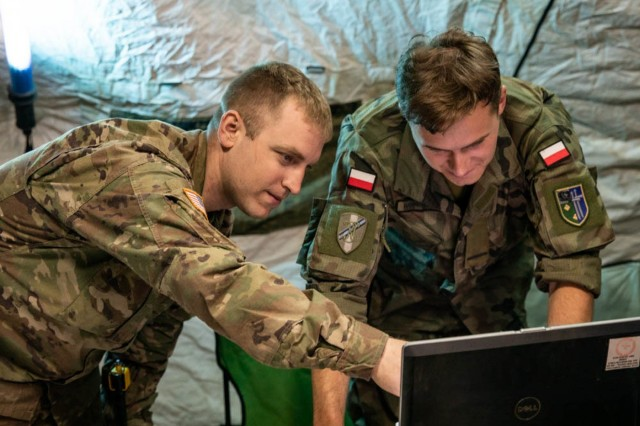 PUMA 19 Battle Captain, Cpt. Greg Martz looks over operations and plans with Polish liason.