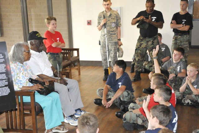 Ronnie and Theodore Lambert (94 and 97 years old respectively) talk to youth attending the Sky Patriot summer camp on Fort Stewart, June 6, at the 3rd ID Museum. During World War II, Theodore Lambert served in the U.S. Army with the 162nd Chemical Smoke Generator Company in Africa, Italy and France.  His wife Ronnie, worked in a factory in Brunswick, Ga, shipping parts to help war effort.