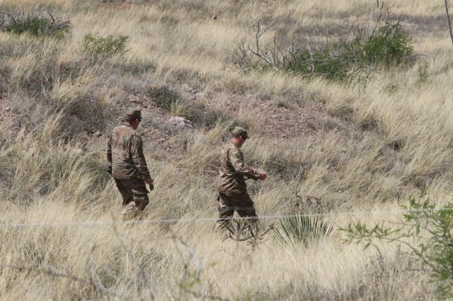 Two Airmen from the 224th Joint Communications Support Squadron, Brunswick, Ga., string HF communication lines across the open terrain, during the HF field Lab on Fort Huachuca, Ariz.