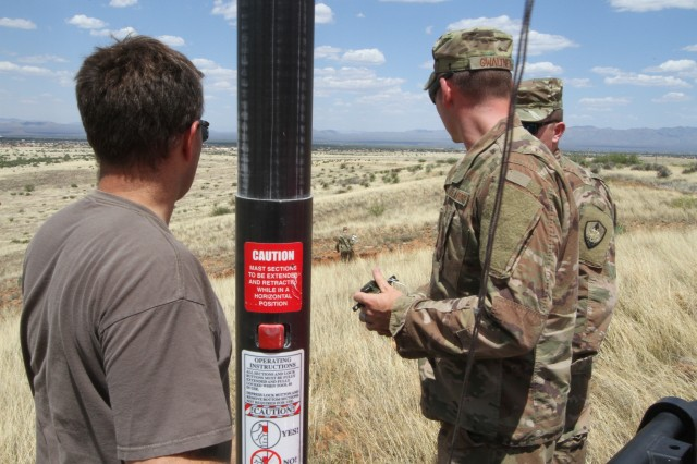 David McGinnis (left), a government contractor supporting the HF lab's efforts, and Air Force Master Sgt. Mike Barber and Tech. Sgt. Neil Howard, watch as Tech. Sgt. Mike Barber (far background), runs the HF communication wire across open ground, during the HF field Lab on Fort Huachuca, Ariz.  All airmen are from the 224th Joint Communications Support Squadron, Brunswick, Ga.