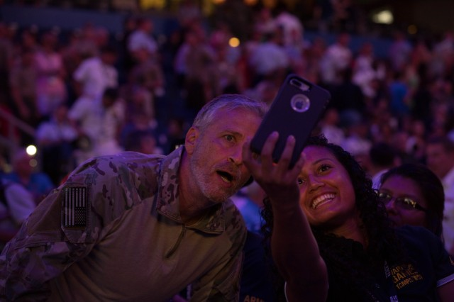 Comedian Jon Stewart takes a picture with a member of Team Army during the opening ceremony at Amalie Arena in Tampa, Florida, June 22, 2019, during the 2019 Department of Defense Warrior Games. The DoD Warrior Games are conducted June 21-30, hosted by Special Operations Command, Tampa, Florida. It is an adaptive sports competiton for wounded, ill, and injured service members and veterans. Approximately 300 athletes, representing teams from the Army, Marine Corps, Navy, Air Force, Special Operations Command, United Kingdom Armed Forces, Australian Defense Force, Canadian Armed Forces, Armed Forces of the Netherlands, and the Danish Armed Forces will compete in archery, cycling, shooting, sitting volleyball, swimming, track, field, wheelchair basketball, indoor rowing, and powerlifting. (U.S. Army photo by Spc. Katelyn Strange)
