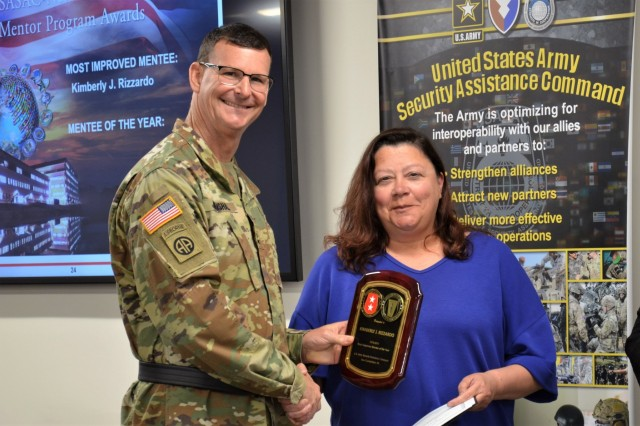 Kim Rizzardo receives a plaque from Maj. Gen. Jeff Drushal, commander if the Security Assistance Command, for being named the Most Improved Mentee.