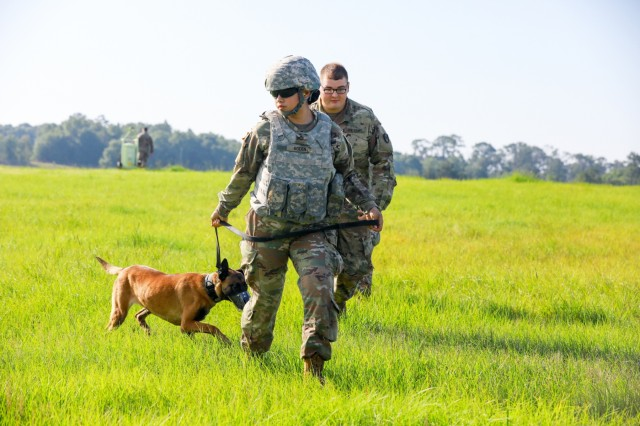 FORT BENNING, Ga. -- Pfc. Samantha Roden, 905th Military Working Dog Detachment at Fort Knox, Kentucky, leads Tina during helicopter familiarization training. Fifteen military working dog teams from across the U.S. Army and the Connecticut Army National Guard performed training June 17, 2019, at Fort Benning here in preparation of deployment. Military working dog teams are used in garrison and combat support missions, including area security, movement and mobility support operations; law and order; and force protection, including narcotic, human, landmine, firearm, ammunition and explosive detection. (U.S. Army photo by Markeith Horace, Maneuver Center of Excellence, Fort Benning Public Affairs)