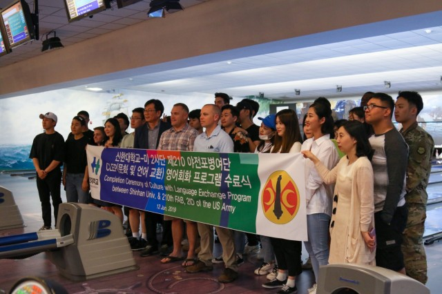 Students from Shinhan University pose for a group photo with 210th Field Artillery Brigade Soldiers at the closing ceremony for the Culture with Language Exchange Program, June 12, at Camp Casey. More than 30 Soldiers and students came to the Camp Casey bowling alley for the closing ceremony. (U.S. Army photo by Sgt. Osvaldo Martinez)