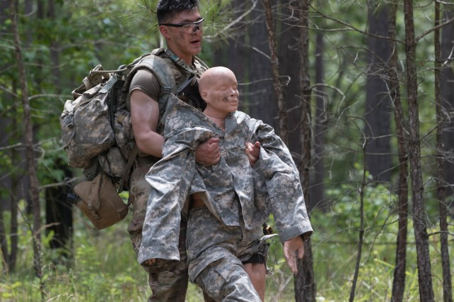 Sgt. Darren Kim, an infantryman with the 101st Airborne Division (Air Assault), carries a casualty to a litter after receiving contact during day two of the 2019 XVIII Airborne Corps Noncommissioned Officer and Soldier of the Year Competition at Fort Bragg, N.C. June 25, 2019. The competition places the best of the best against each other in a grueling week of mental and physical tests. (U.S. Army Photo by Pfc. Joshua Cowden / 22nd Mobile Public Affairs Detachment)
