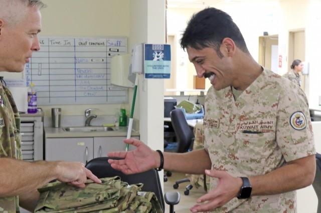 U.S. Army Maj. Scott Mateosky, 349th Combat Support Hospital, presents Awadh Hamoud, a Kuwait Army nurse, with Army hospital scrubs during a visit to Camp Arifjan's  U.S. Military Hospital - Kuwait June 17, 2019. (U.S. Army National Guard photo by Sgt. Connie Jones)