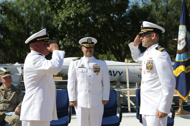"""Outgoing Commander Anthony Holmes (left) salutes his replacement, Commander Colin Monk, during a June 20, 2019, Change of Charge Ceremony at White Sands Missile Range, N.M. Looking on is guest speaker Captain Rafael """"Ray"""" Acevedo, Commanding Officer, Naval Surface Warfare Center, Port Hueneme Division, Calif."""