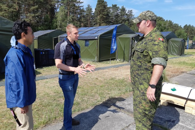 Blane Wilson (left) and Joseph Vitale (middle), both electronics engineers with U.S. Army CCDC C5ISR Center, talk with a Canadian soldier during Capable Logistician 2019 in June 2019 at Drawsko Pomorskie Training Grounds, Poland.