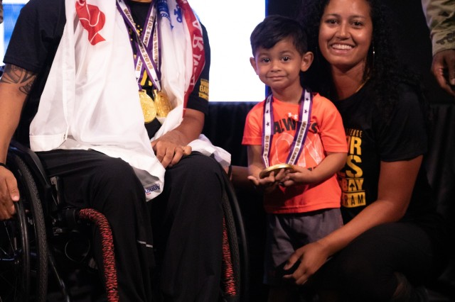 U.S. Army retired Staff Sgt. Joel Rodriguez poses with his with wife Liannie and son Elijah after receiving his medals, June 25, 2019 at the Tampa Convention Center, during the 2019 Department of Defense Warrior Games in Tampa, Florida. Approximately 300 athletes representing teams from the Army, Marine Corps, Navy, Air Force, Special Operations Command, United Kingdom Armed Forces, Australian Defence Force, Canadian Armed Forces, Armed Forces of the Netherlands, and the Danish Armed Forces are participating in 13 events throughout the competition. (U.S. Army photo by Staff Sgt. Michael Loggins)